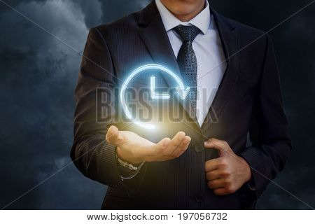 Businessman Hand Holds The Icon Of Hours With Arrow.