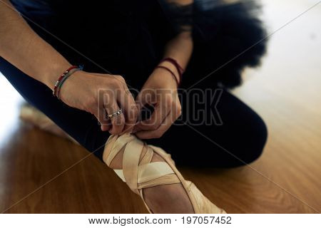 Close-up shot of unrecognizable ballet dancer sitting on floor and tying pointe shoes