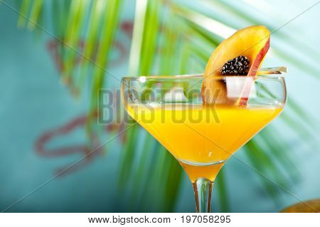 Summer  Cocktail -  Pornstar Martini. Drink with Passion fruit, Vodka, Liquor, Vanilla Syrup, Champagne and Lime Juice. Tropical Leaf on Background