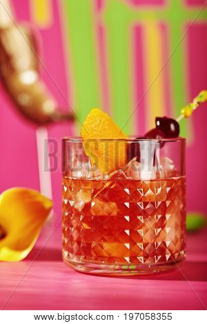 Alcohol Cocktail - Old Fashioned Cocktail or Manhattan Cocktail. Bourbon, Cane Sugar, Bitter and Orange Peel. Cocktail with Fruit and Flower on Pink Background