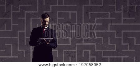 Businessman with computer tablet standing over labyrinth background. Business, strategy, concept.