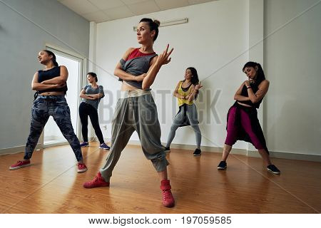 Group of talented hip-hop dancers wrapped up in rehearsal before important on-stage performance, interior of spacious dance hall on background