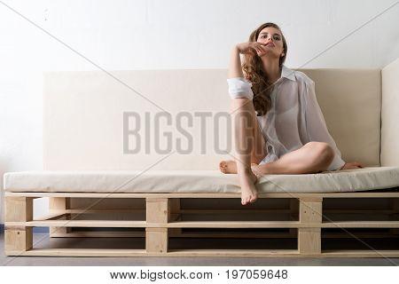 Seductive brunette wearing sexy white shirt sitting on beige wooden sofa studio shot