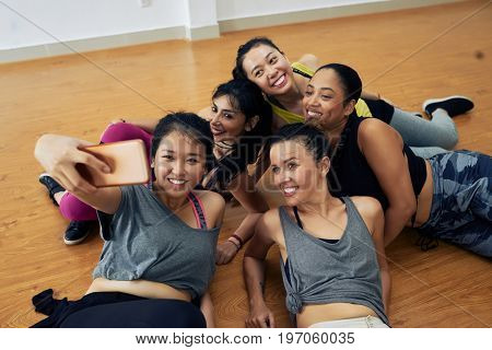 Group of pretty hip-hop dancers taking selfie on smartphone while having fun after intensive training in dance hall