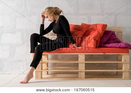 Slim blonde in black office suit sitting on a wooden sofa in a wistful pose