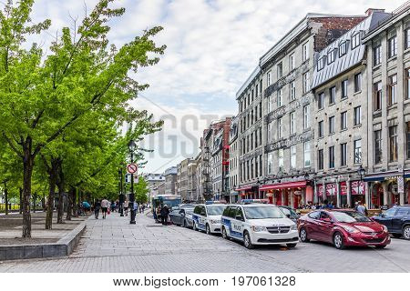 Montreal, Canada - May 27, 2017: Old Town Area With Restaurants, Police Cars On Road, And People Wal