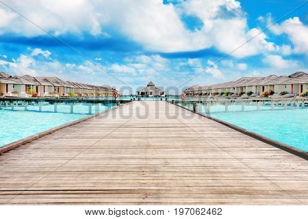 Wooden pontoon and modern beach houses on piles at tropical resort