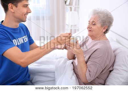 Young male volunteer feeding elderly woman in light room