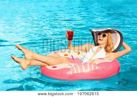 Beautiful young woman with glass of cocktail relaxing on inflatable donut in pool