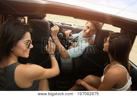 Group of young happy people having fun together by driving a car