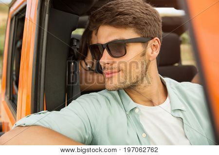 Smiling young man in sunglasses sitting on a front seat in a car with his friends on a background