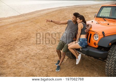 Beautiful young couple embracing while leaning on their car and pointing finger away outdoors