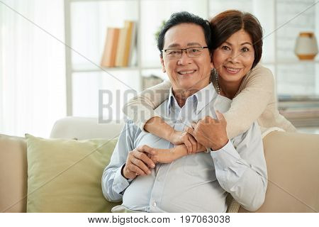 Portrait of happy aged Vietnamese couple smiling and looking at camera