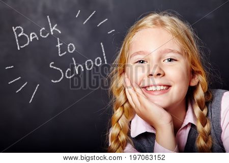 Portrait of a funny schoolgirl on blackboard background. School and education