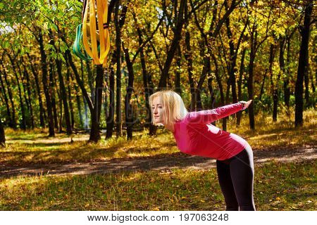 Young athletic woman warming-up before suspension training in park