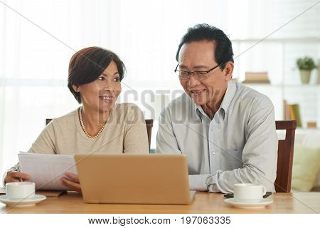 Aged husband and wife using laptop when reviewing bank accounts