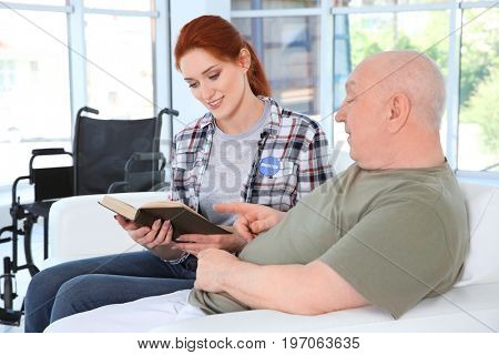 Young female volunteer reading book to senior man in light room