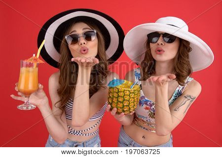 Picture of young smiling two women standing isolated over red background. Looking at camera drinking cocktails blowing kisses.