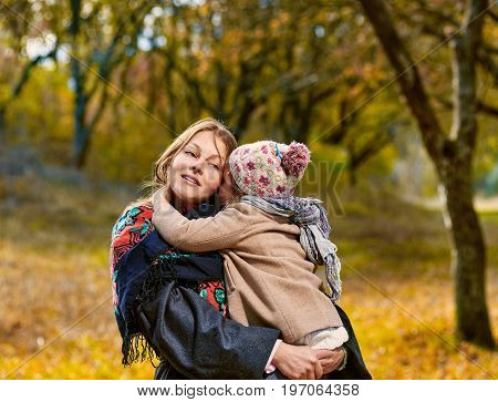 Mother holding her cute little daughter during walk in park