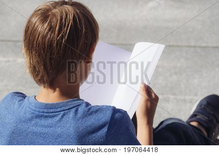 Schoolboy studying, reading book outdoors. Back view