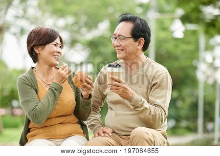 Cheerful Asian couple having snacks and coffee in city park