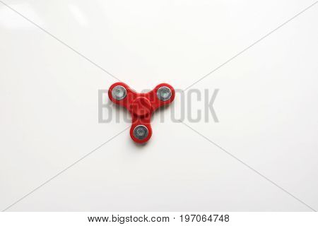 Red  Hand Spiner. Stress relieving toy on white background. Close-up. Top view. Stock photo.