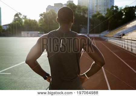Back view of a young male sportsman standing at the stadium race track with hands on hips