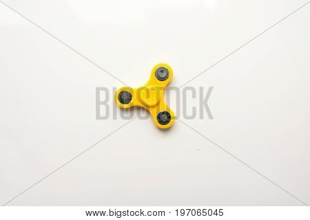 Yellow  Hand Spiner. Stress relieving toy on white background. Close-up. Top view. Stock photo.