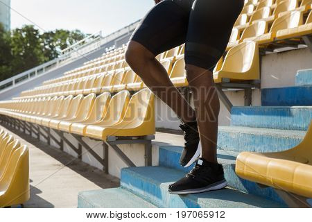 Cropped image of a young man's legs walking down the stairs at the stadium