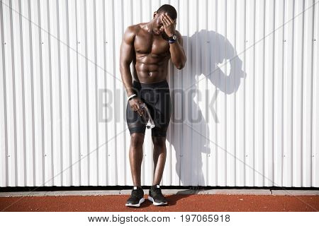 Full length of a tired exhausted afro american male athlete holding water bottle while standing against white wall