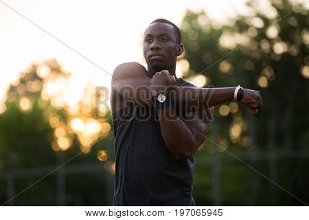 Concentrated afro american sportsman stretching hands at the stadium