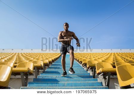 Young male athlete exercising by running downstairs at the stadium