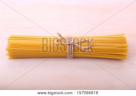 A top view on long pasta noodles tighten with a little rope with a bowtie. Nutritious noodles on a light brown wooden background. Delicious flour pasta. Traditional italian cuisine.