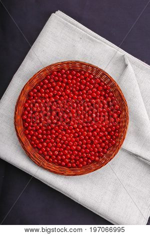 A top view of a composition of a wicker basket with juicy red currant on a dark blue background. Sour and ripe red currant full of nutritious vitamins. Healthy and tasty ingredients.