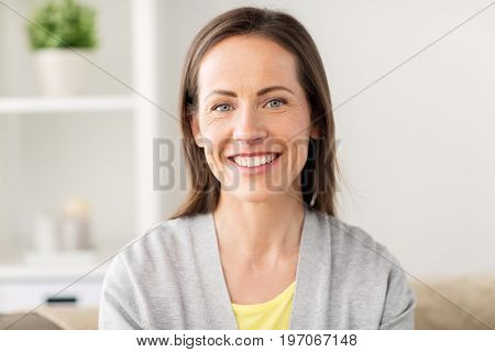 people, emotion and facial expression concept - happy smiling middle aged woman at home