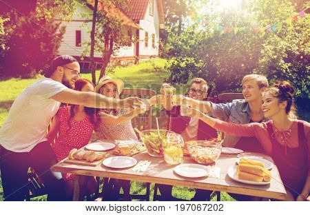 summer, holidays, celebration people and food concept - happy friends having garden party and clinking glasses