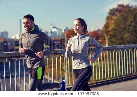 fitness, sport, people and lifestyle concept - happy couple running outdoors