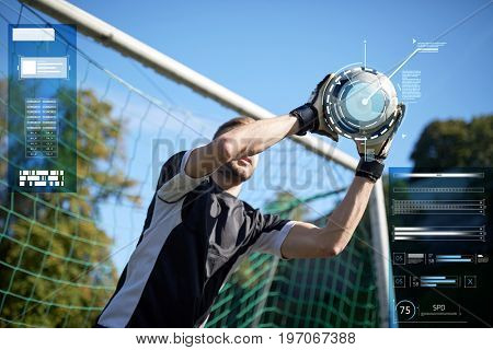 sport, technology and people concept - soccer player or goalkeeper catching ball at goal on football field