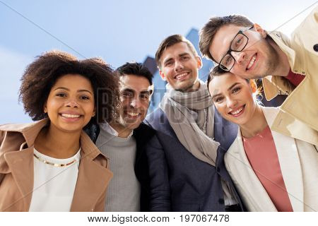 business, education and corporate concept - international group of happy smiling people or friends on city street