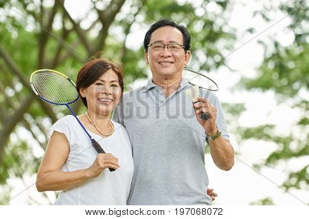 Portrait of sporty aged Asian couple with badminton rackets