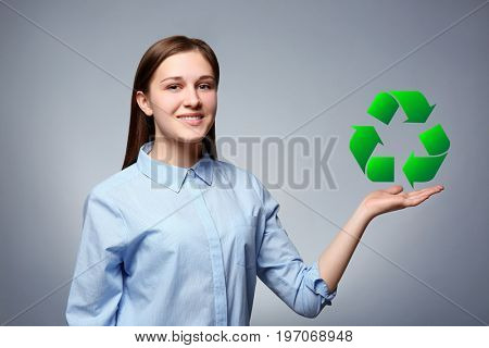 Woman holding sign of recycling on grey background. Ecology and environment conservation