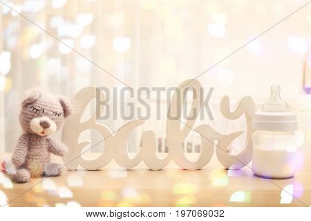 Knitted baby toy with decor and bottle of milk on table in bedroom. Holidays celebration concept