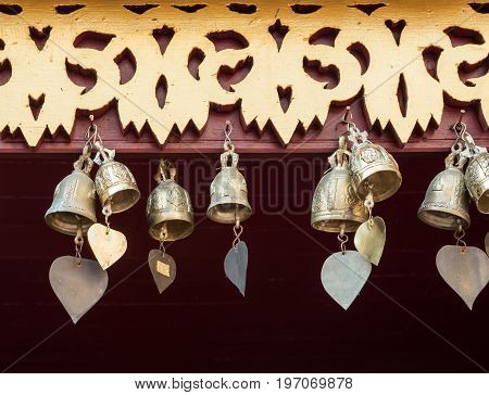 Small brass bell with the heart shape tail for decorate on the wooden eaves of the Thai church.(Public area not required Property Release)