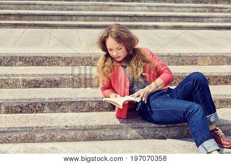 Pretty girl reading a book while sitting on the stairs.  youth lifestyle