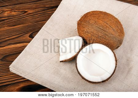 Nutritious cracked coconuts on a brown table. Tasteful and tropical nuts on a light gray piece of cloth on a dark wooden background. Healthful and organic summer fruits.
