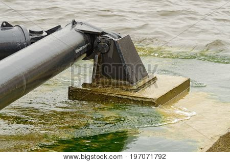 On the water is a helipad. It is secured to the shore using a metal mount .