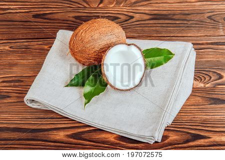 A couple of refreshing tropical coconuts on a gray fabric on wooden background. Tasteful and nutritious coconuts with fresh green leaves. Organic ingredients for vegetarian dishes.