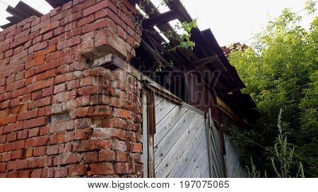 Old crumbling brick house, abandoned building background. Brick wall