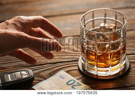 Man's hand reaching to glass of whiskey or alcohol drink with ice cubes and car key on rustic wooden table. Drink and drive and alcoholism concept. Safe and responsible driving concept.
