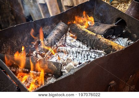 ignition of firewood outdoors. preparing firewood for cooking barbecue. fry meat on the grill. background of wood.